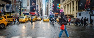 Mann går over fotgjengerfelt i gate med gule taxier i New York
